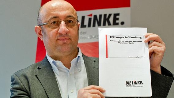 """Mehmet Yildiz, sportpolitischer Sprecher der Linken, präsentiert das Papier """"NOlympia in Hamburg"""""""