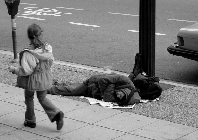 """""""Man sleeping on Canadian sidewalk"""" von The Blackbird (Jay Black) - Flickr. Lizenziert unter CC BY-SA 2.0 über Wikimedia Commons"""