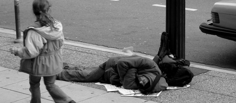 """Man sleeping on Canadian sidewalk"" von The Blackbird (Jay Black) - Flickr. Lizenziert unter CC BY-SA 2.0 über Wikimedia Commons"