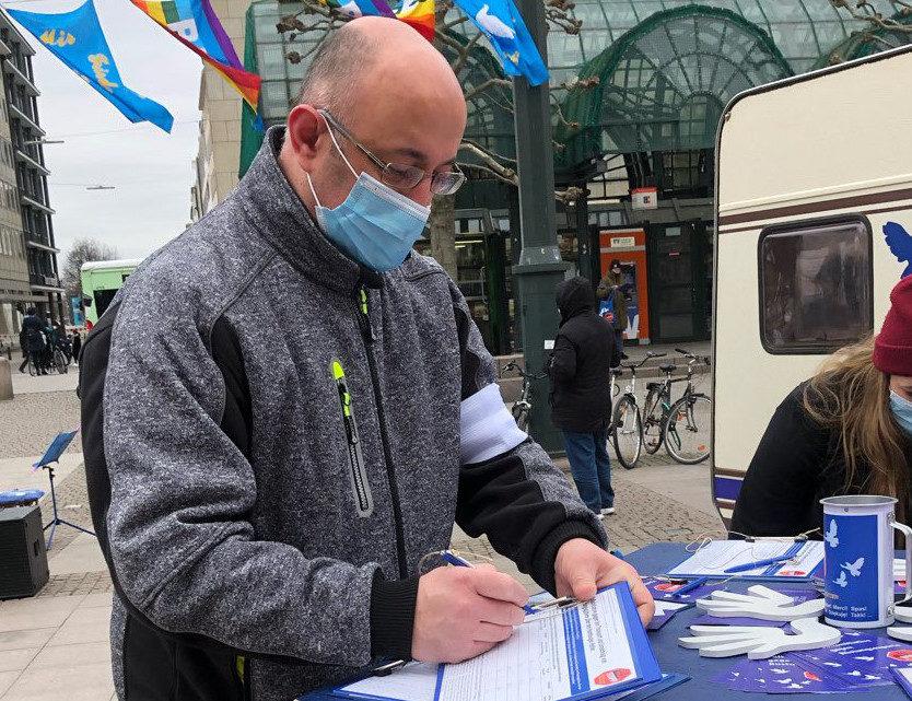 Mehmet Yildiz beim Unterschreiben der Volksinitiative gegen Rüstungsexporte